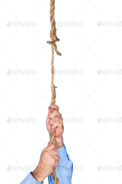 Businessman hanging from frayed rope