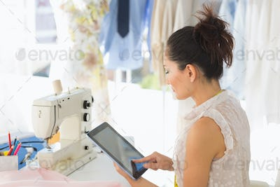 Side view of a young female fashion designer using digital tablet in the studio