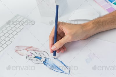 Extreme closeup of a fashion designer working on designs in the studio