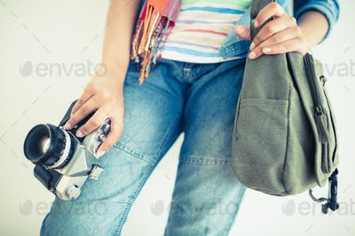 Woman in denim holding camera and shoulder bag on white background