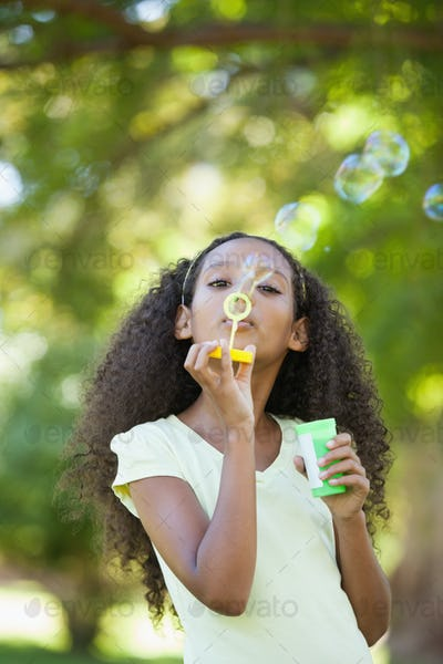 Young girl blowing bubbles in the park on a sunny day
