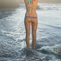 Happy blonde standing on the beach in bikini in tree pose on a sunny day