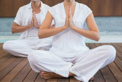 Couple in white sitting in lotus pose with hands together in health spa