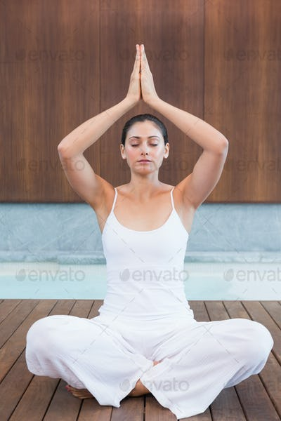 Peaceful woman in white sitting in lotus pose in health spa