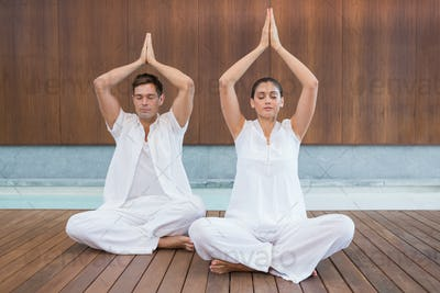 Attractive couple in white sitting in lotus pose with hands together in health spa