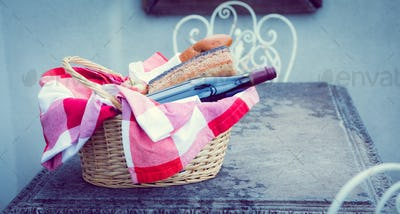 Picnic basket of red wine and bread on table outside