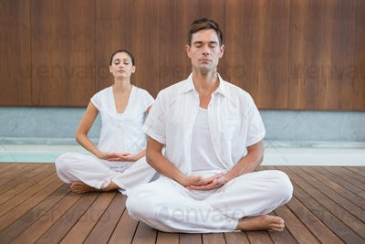 Peaceful couple in white sitting in lotus pose together in health spa