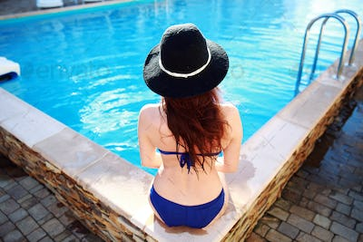 Back view portrait of a young woman sitting on the ledge of the pool