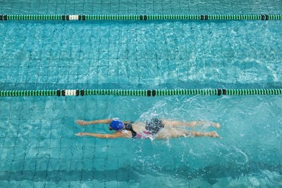 Female swimmer training by herself in swimming pool at the leisure centre