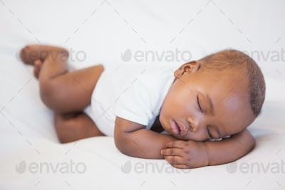 Baby boy sleeping peacefully on couch at home in the living room