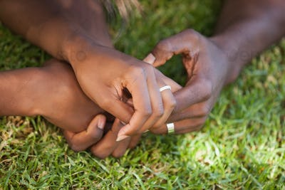 Couple holding hands on the grass on a sunny day