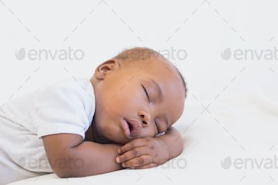 Adorable baby boy sleeping peacefully at home in the living room
