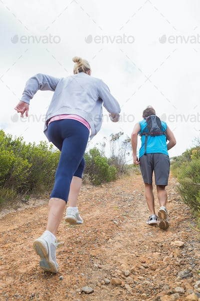 Fit attractive couple jogging up mountain trail on a sunny day