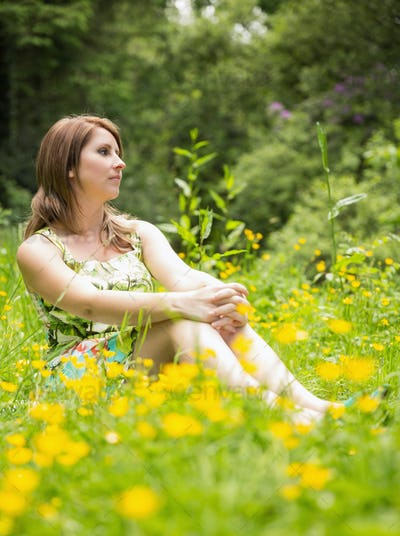 Cute young woman relaxing in field against the trees