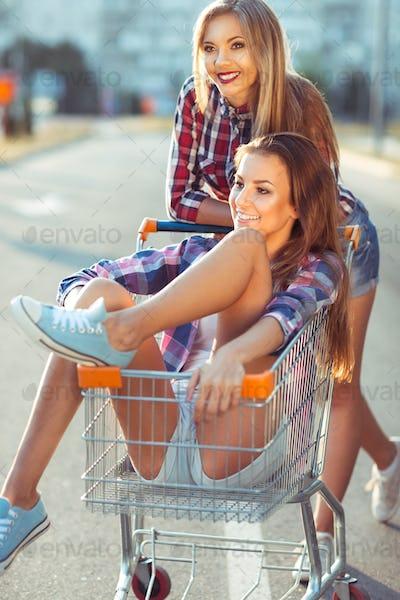 Two happy beautiful teen girls driving shopping cart outdoors