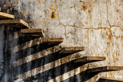 Stairs casting shadow on old weathered wall