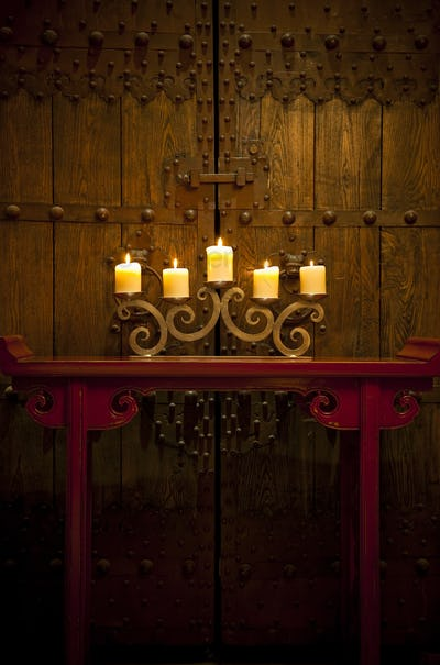 Candles burning on table in front of old rustic door