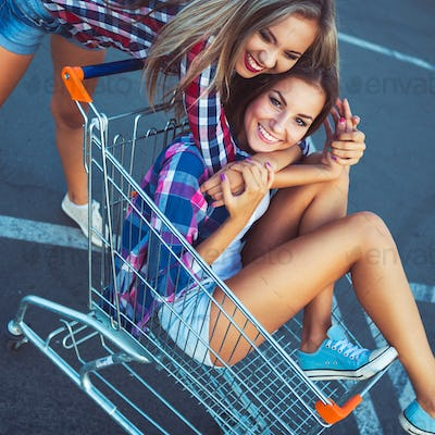 Two happy beautiful girls in shopping cart outdoors, lifestyle c
