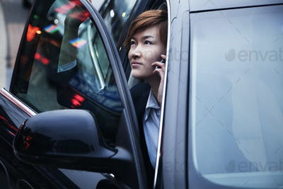 Businesswoman exiting car while on the phone
