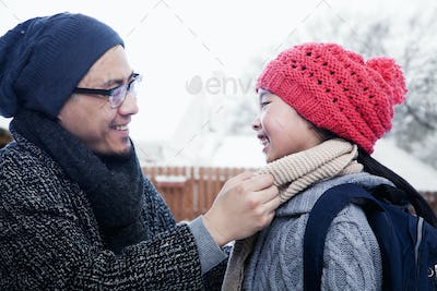Father fixing daughter's scarf