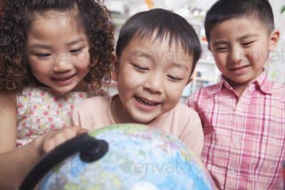 Close Up of Students Looking at a Globe