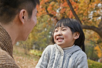 Father and daughter looking at each other in the park, autumn