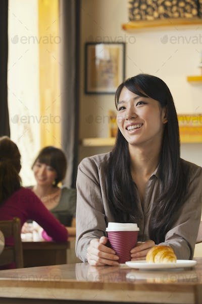 Beautiful young woman holding coffee cup in a coffee shop, Beijing