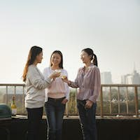 Young Women Toasting Each Other on Rooftop at Sunset