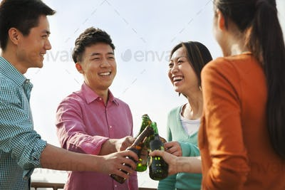 Friends Toasting Each Other on a Rooftop