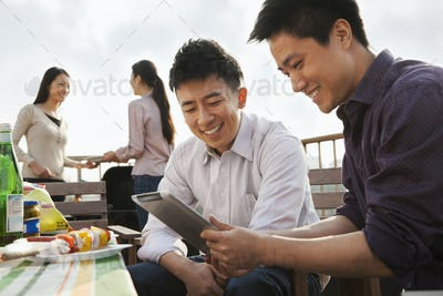 Friends Using Digital Tablet at Rooftop Barbecue