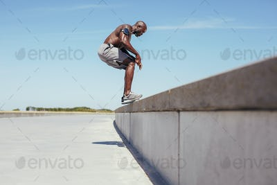 Shirtless young athlete doing jumping workout