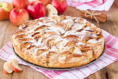 apple pie on a wooden background with cinnamon