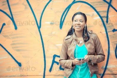 beautiful african young woman listening music earphones