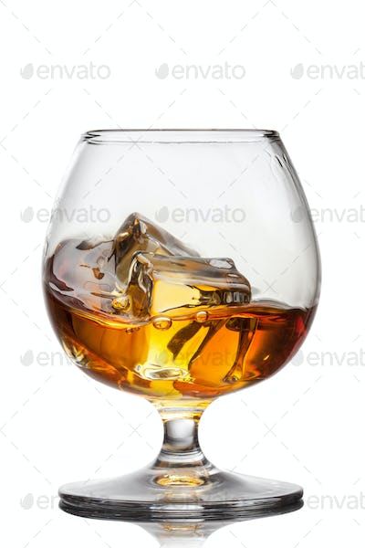 Splash of whiskey with ice in glass isolated