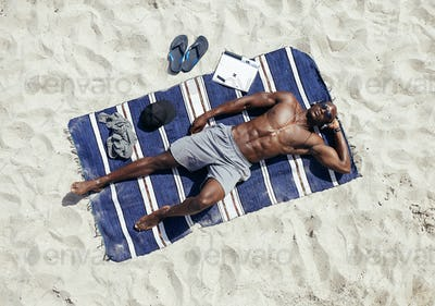 Young man relaxing on mat at beach