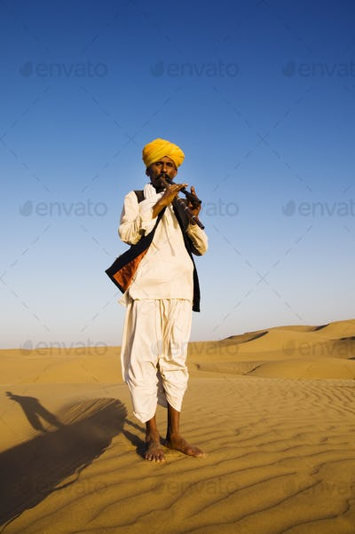 Indigenous Indian Man Playing Wind Pipe In A Desert