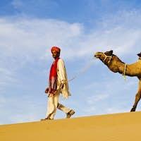 Indigenous Indian Man Walking Through The Desert With His Camel