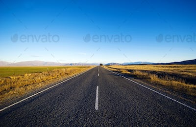 Continuous Road In A Scenic With Mountain Ranges Afar