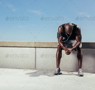 Tired young runner leaning over to catch his breath