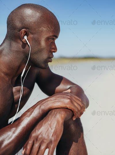 African man wearing earphones sitting alone