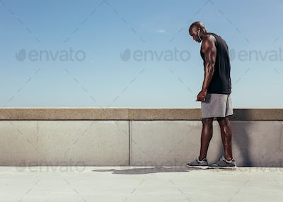 Muscular man on walkway getting ready for his run