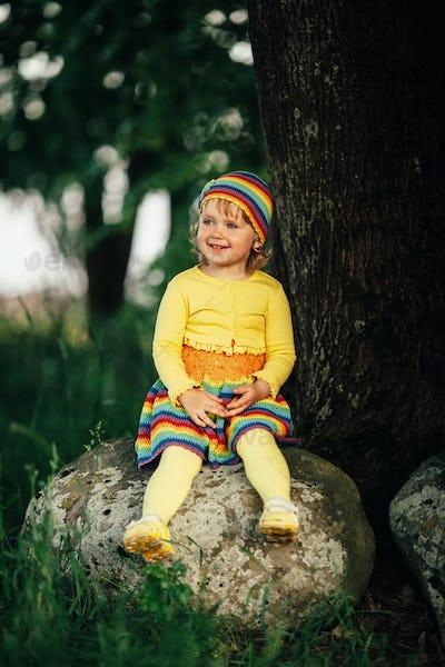 little girl sitting on big stone