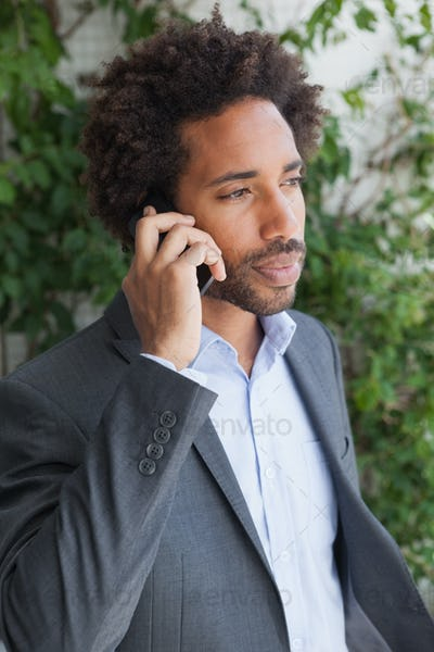 Handsome businessman on the phone on a sunny day