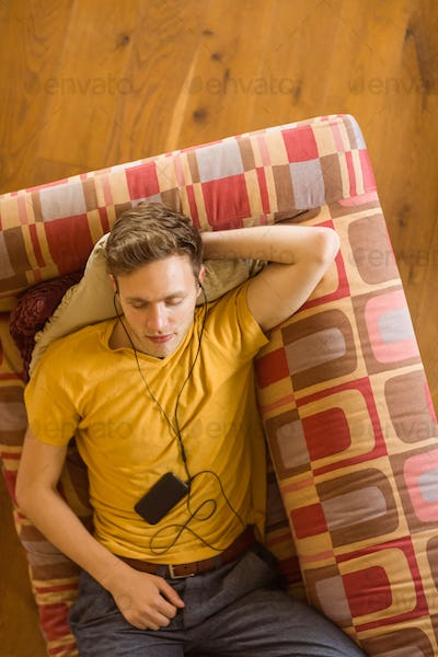 Young man listening to music on his couch at home in the living room