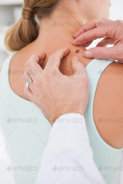Doctor examining a brown spot on a patients neck