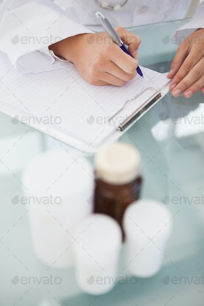 Doctor writing out prescriptions from pill bottles
