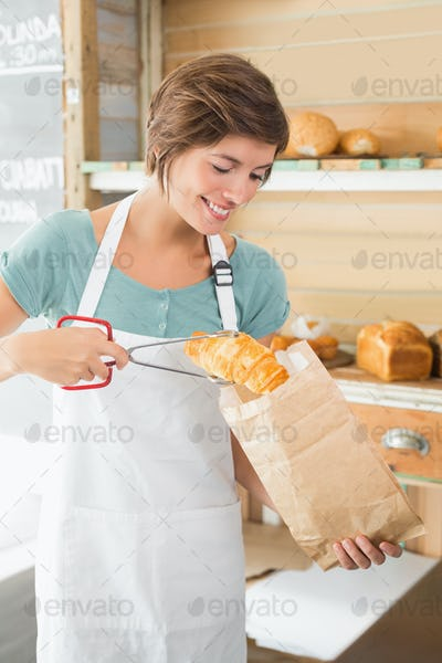 Pretty waitress putting croissant in paper bag at the coffee shop