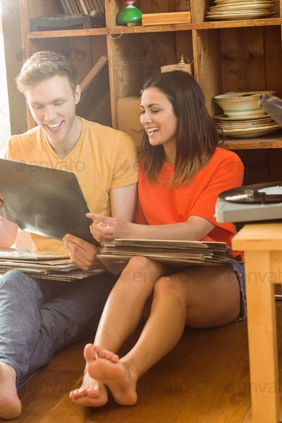 Young couple looking at vinyl collection at home in the living room