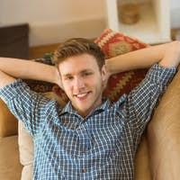 Young man relaxing on his couch at home in the living room