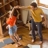 Young couple dancing to vinyl records at home in the living room